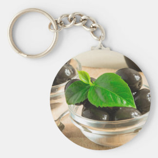 Brown pickled olives in a transparent cups keychain