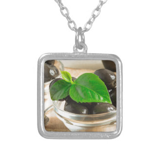 Brown pickled olives in a transparent cups silver plated necklace
