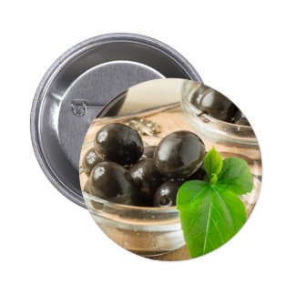 Brown pickled olives on the old wooden background button