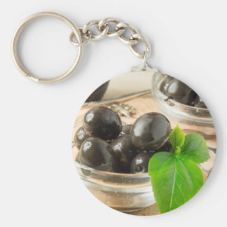 Brown pickled olives on the old wooden background keychain