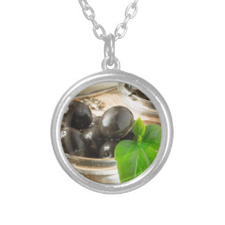 Brown pickled olives on the old wooden background silver plated necklace