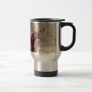 Brown scottish highlander cow standing in spring travel mug