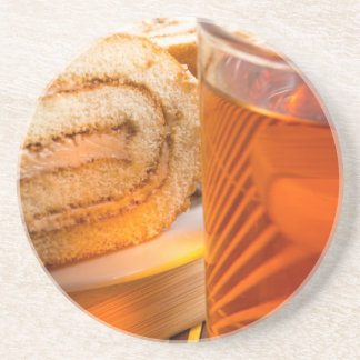 Brown sponge cake and cup of hot tea coaster