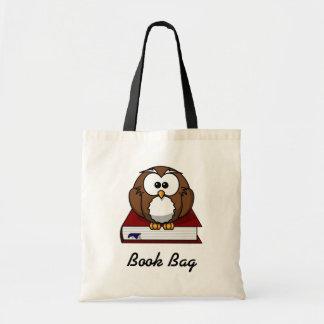 Brown y búho blanco que se sientan en un libro