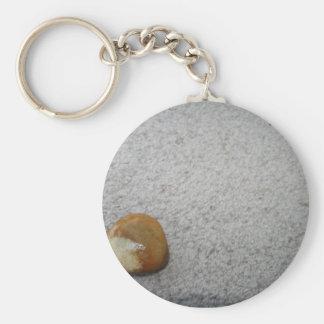 Brown y roca redonda blanca en la alfombra poner c llaveros personalizados