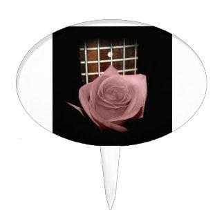 Brownish pink single rose against fretboard cake picks