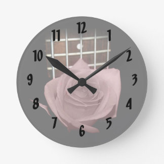 Brownish pink single rose against fretboard round wall clock
