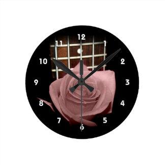 Brownish pink single rose against fretboard round clock