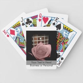 Brownish pink single rose against fretboard card deck