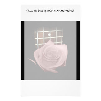 Brownish pink single rose against fretboard stationery paper