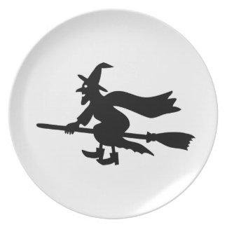 Bruja con la escoba vuela plato de comida