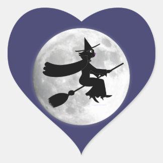 Bruja del gato negro en la escoba delante de la pegatina en forma de corazón