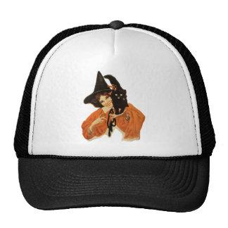 Bruja hermosa del vintage con el gato negro en gorras de camionero