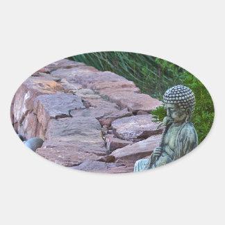 Buda meditating by the stream oval sticker