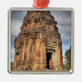 Buddhist monk standing in doorway of temple metal ornament