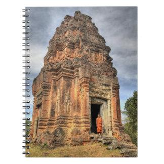Buddhist monk standing in doorway of temple notebook