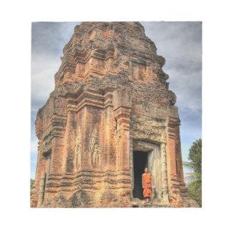Buddhist monk standing in doorway of temple notepad