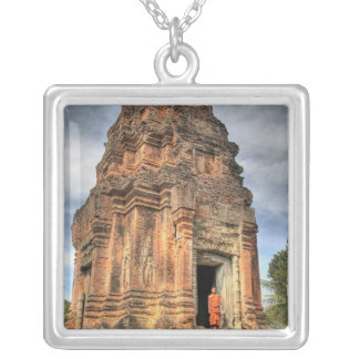 Buddhist monk standing in doorway of temple silver plated necklace