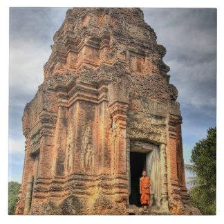 Buddhist monk standing in doorway of temple tile