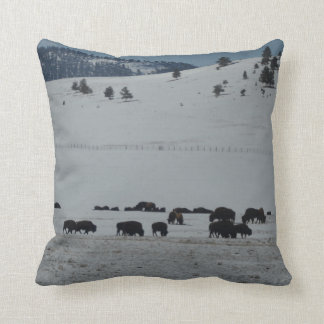 Buffalo grazing on snow covered mountain throw pillow