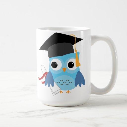 Búho azul con la taza de la graduación del diploma
