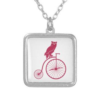 Búho que se sienta en una bici del vintage colgante cuadrado