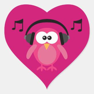 Búho rosado con los auriculares y las notas pegatina en forma de corazón