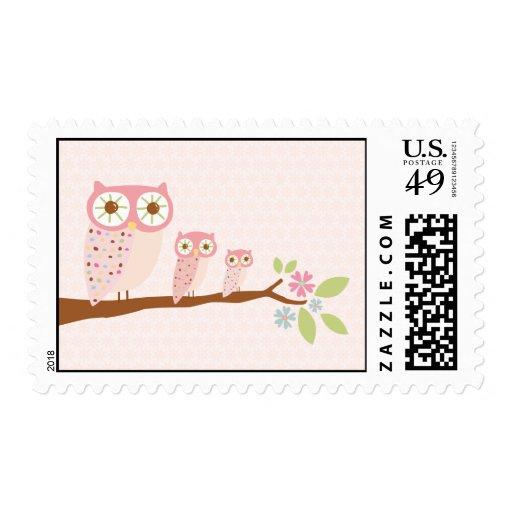 Búhos rosados en un sello de la rama