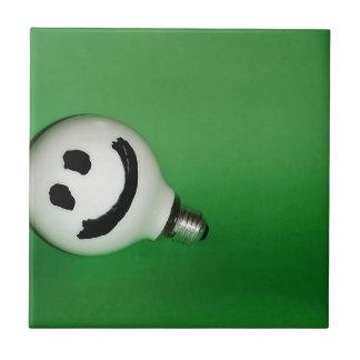 Bulbo sonriente blanco en fondo verde teja  ceramica