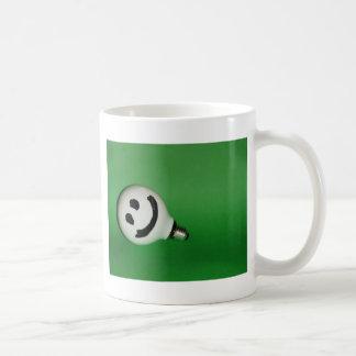 Bulbo sonriente blanco en fondo verde taza de café