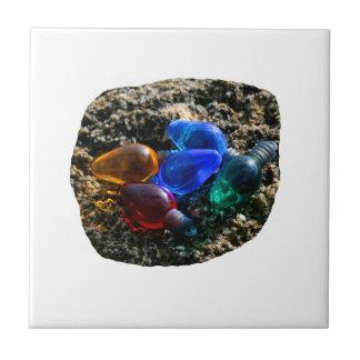 Bulbos coloridos del navidad en fotografía de la a teja cerámica