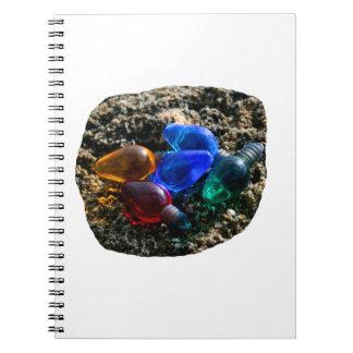 Bulbos coloridos del navidad en fotografía de la a libro de apuntes con espiral