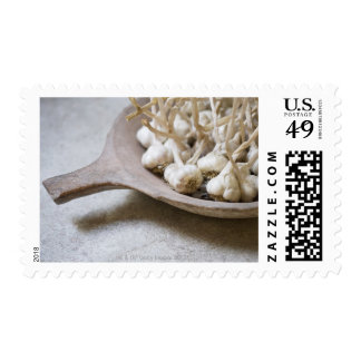 Bulbos del ajo en un cuenco de la loza de barro timbre postal
