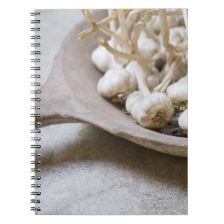Bulbs of garlic in an earthenware bowl note book
