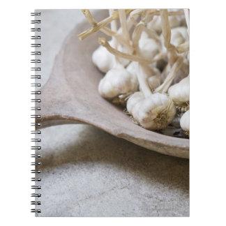 Bulbs of garlic in an earthenware bowl spiral notebook