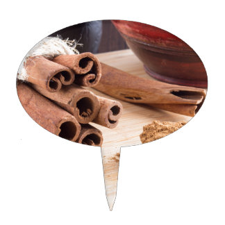 Bunch of cinnamon sticks and vintage silver spoon cake topper