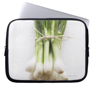 Bunch of spring onions on white chopping board computer sleeves