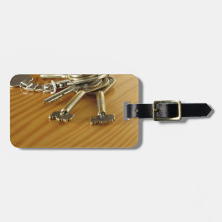 Bunch of worn house keys on wooden table bag tag