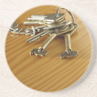 Bunch of worn house keys on wooden table coaster
