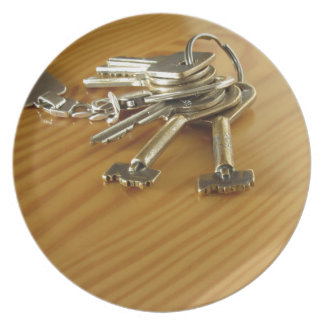 Bunch of worn house keys on wooden table dinner plate