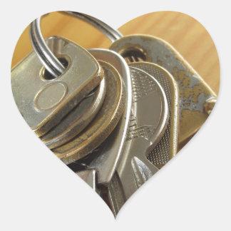 Bunch of worn house keys on wooden table heart sticker