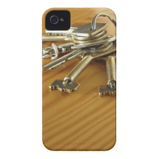 Bunch of worn house keys on wooden table iPhone 4 cover