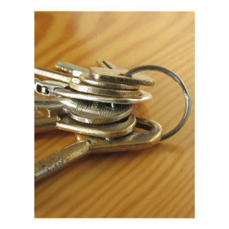 Bunch of worn house keys on wooden table letterhead