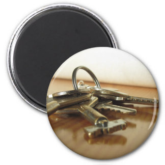 Bunch of worn house keys on wooden table magnet