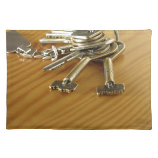 Bunch of worn house keys on wooden table placemat