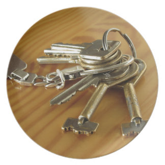 Bunch of worn house keys on wooden table plate