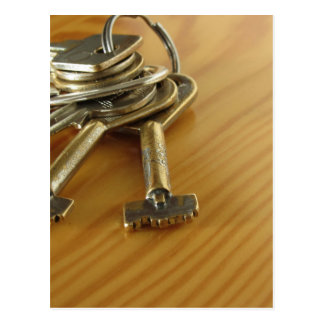 Bunch of worn house keys on wooden table postcard