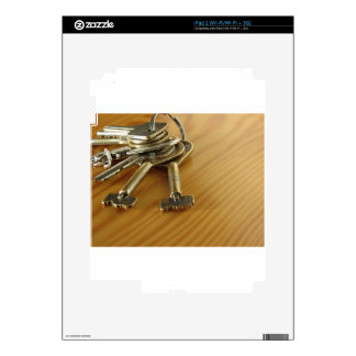 Bunch of worn house keys on wooden table skin for iPad 2