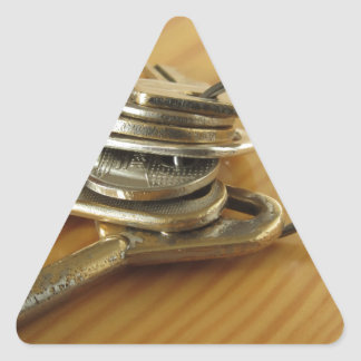 Bunch of worn house keys on wooden table triangle sticker