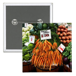 Bunches of carrots and vegetables on market button